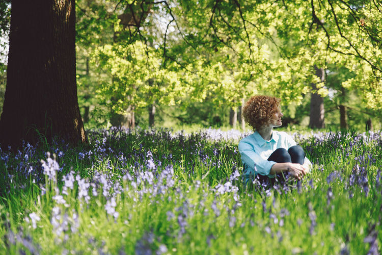 Woman Sitting Amidst Plants At Forest
