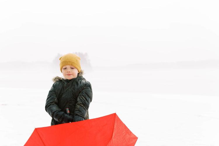 Portrait of senior woman in snow against sky