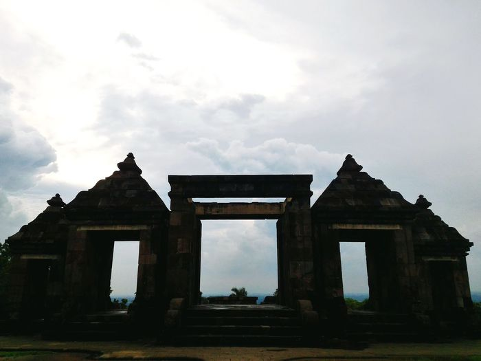 Low angle view of old building against cloudy sky