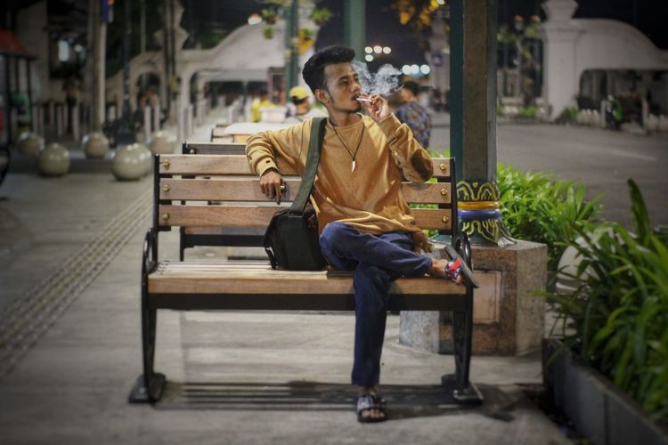 Young man smoking while sitting on bench in city at night