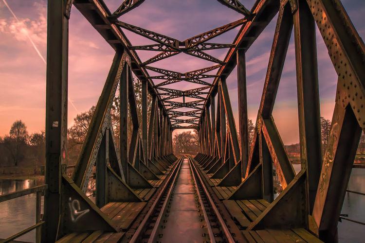 Railway bridge against sky during sunset