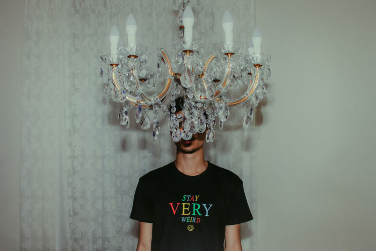 Teenage boy standing by chandelier at home