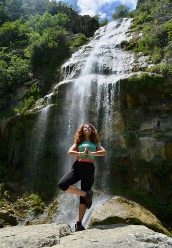 Full length of woman yoga by a waterfall