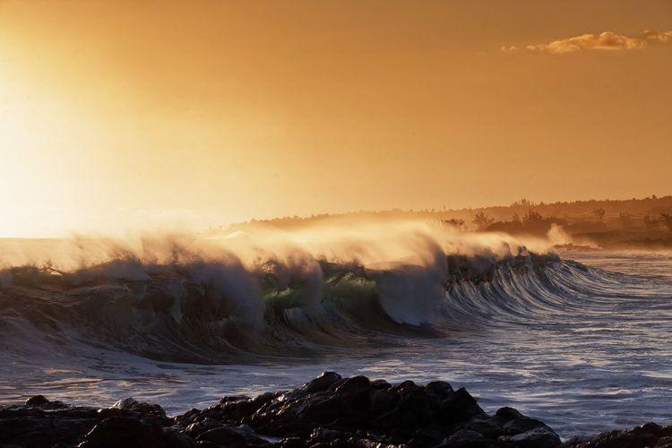Waves splashing on shore against sky during sunset