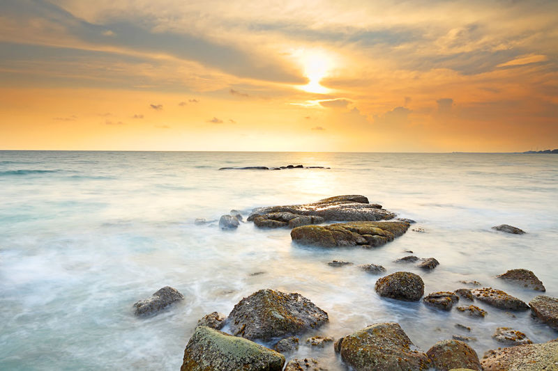 Beautiful seascape with sunset on the rocky shore of a tropical beach and Island Sea Horizon Over Water Water Horizon Scenics - Nature Sky Rock Beauty In Nature Sunset Solid Rock - Object Beach Land Cloud - Sky Tranquility Tranquil Scene Motion Idyllic Nature No People Sun Outdoors Seascape Coastline Sunrise ASIA Thailand Island Beauty In Nature Tranquility Stone