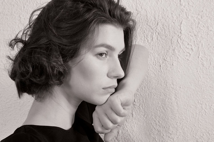 Close-up portrait of a young woman against wall