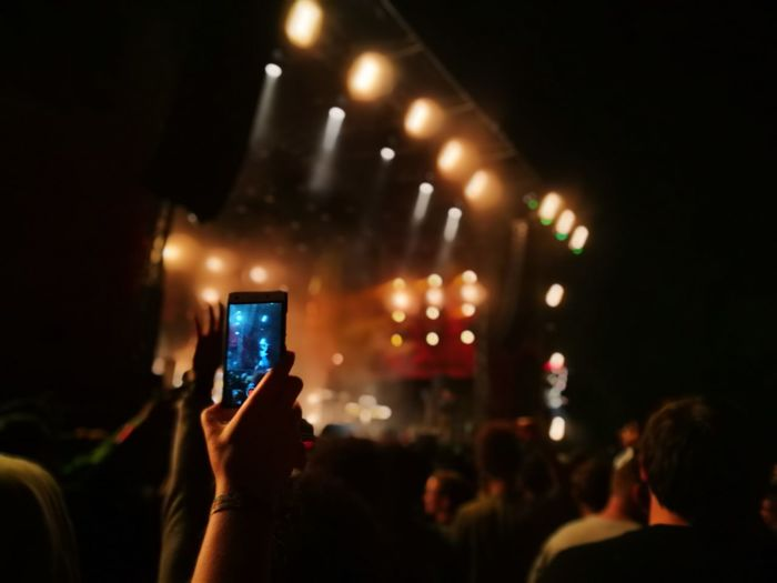 Cropped hand photographing with smart phone during music concert