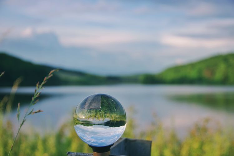 Close-up of crystal ball on lake against sky