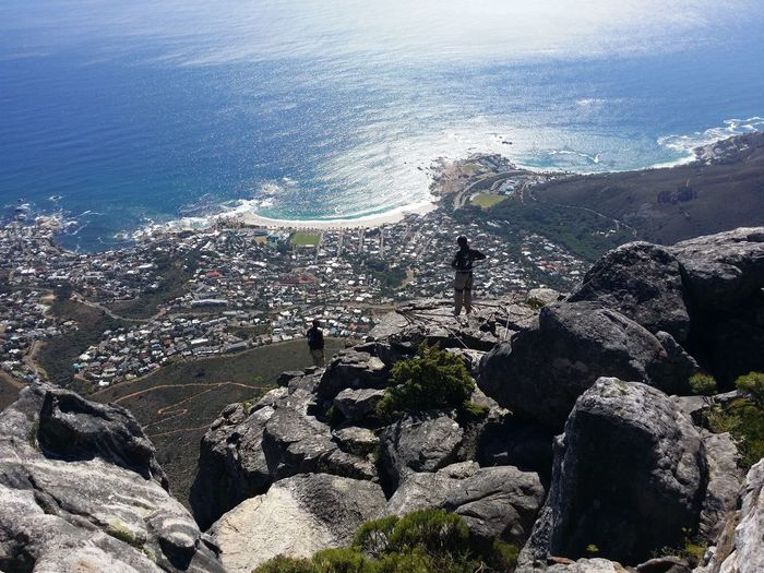 Aerial view of people standing at table mountain against sea on sunny day