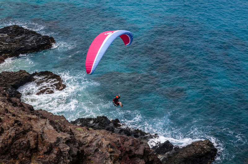 High angle view of man parachuting above sea