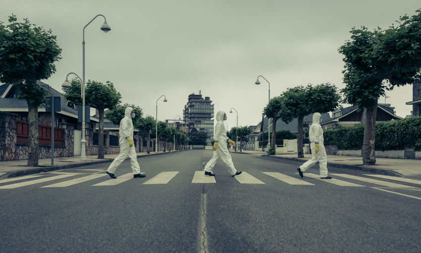 Man and women walking on crosswalk against sky
