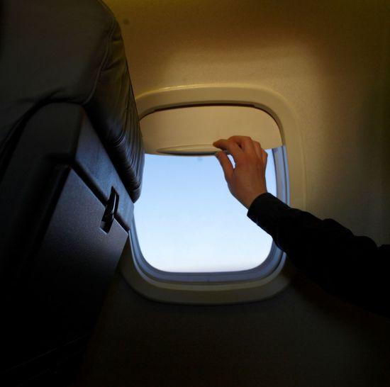 Man closing airplane window