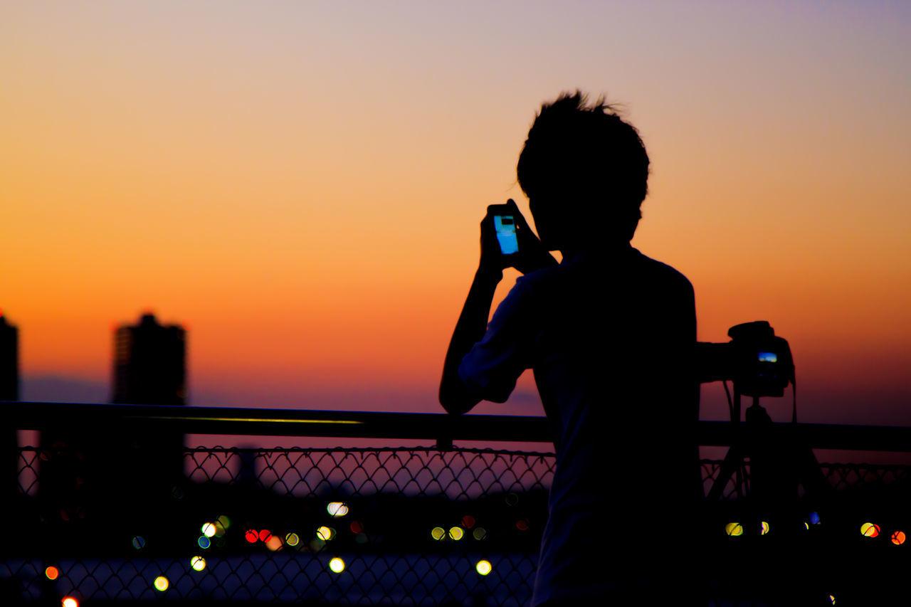 Silhouette man using phone against orange sky