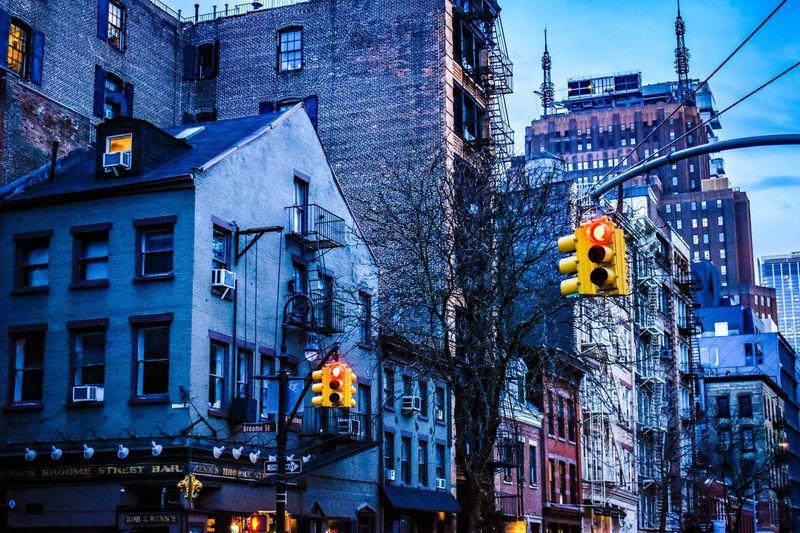 Illuminated street light against buildings in city