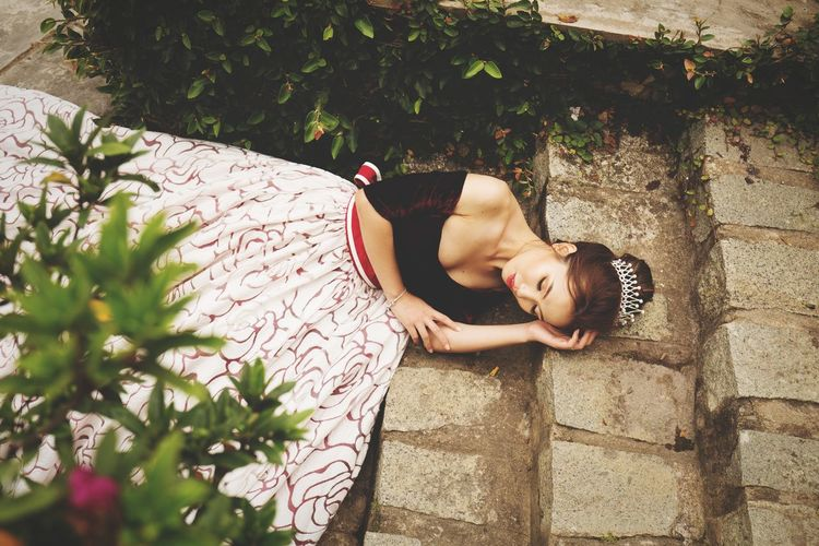 High angle view of beautiful woman wearing gown and tiara while lying on steps