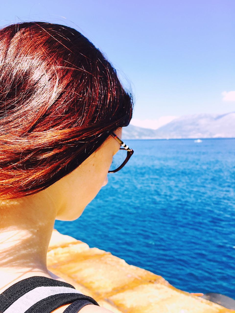 Close-Up Of Woman By Blue Sea Against Clear Sky On Sunny Day