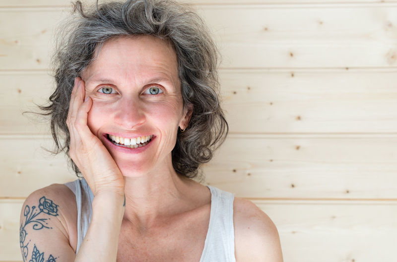 Close-Up Portrait Of Happy Mature Woman With Hand On Chin By Wall
