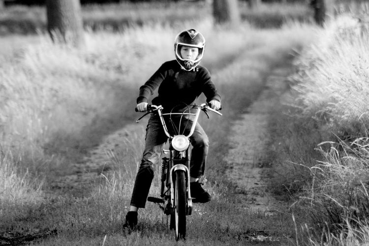 Boy on motor One Person Transportation Headwear Helmet Mode Of Transportation Men Sports Helmet Full Length Front View Riding Ride Leisure Activity Child Sport Males  Nature Childhood Lifestyles Motorcycle Crash Helmet