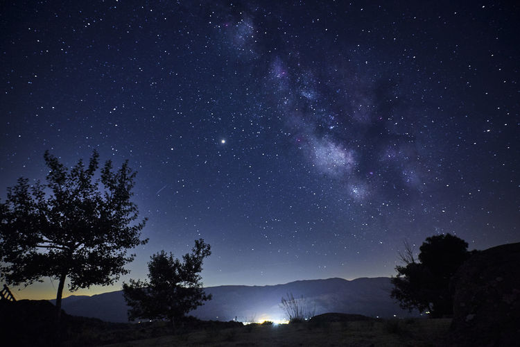 View of the milky way over the lights of a mountain village. concept science, astronomy