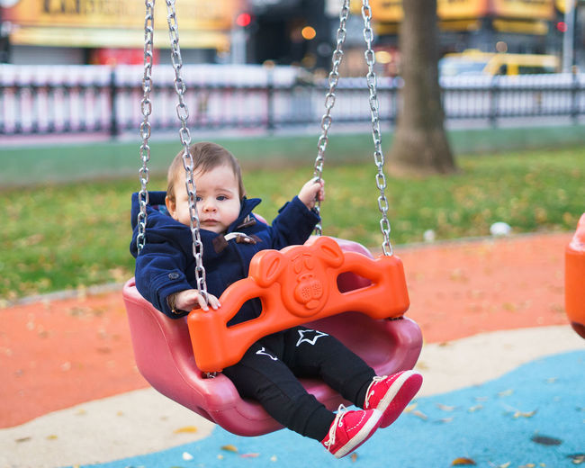 Baby Boy Sitting On Swing At Park