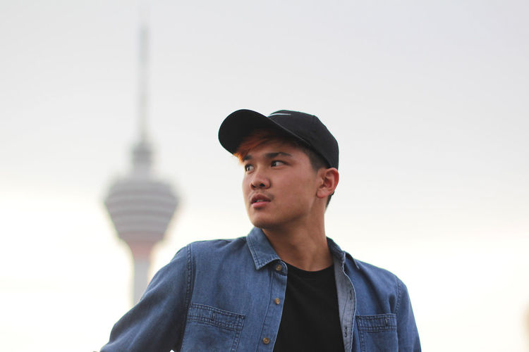 Low angle view of young man looking away while standing against menara kuala lumpur tower