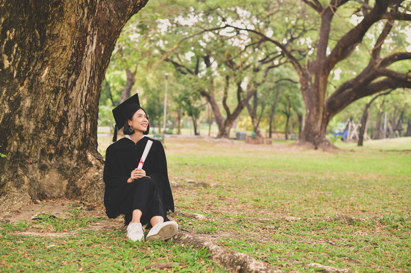 Smiling Young Woman In Graduation Gown Holding Certificate While Sitting On Grassy Field At Park