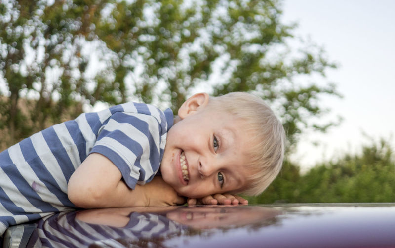 Happy Caucasian boy lies on car roof and looks at camera Happy Looking At Camera Roof Blond Hair Boys Car Caucasian Child Childhood Children Only Day Elementary Age Happiness Headshot Leisure Activity Lies Lifestyles Looking At Camera Looks At Camera Nature One Boy Only One Person Outdoors People Portrait Real People Smiling Tree