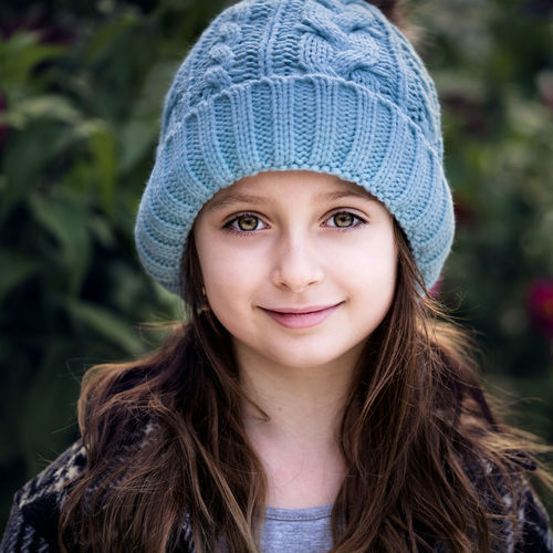 Portrait of cute smiling girl standing outdoors
