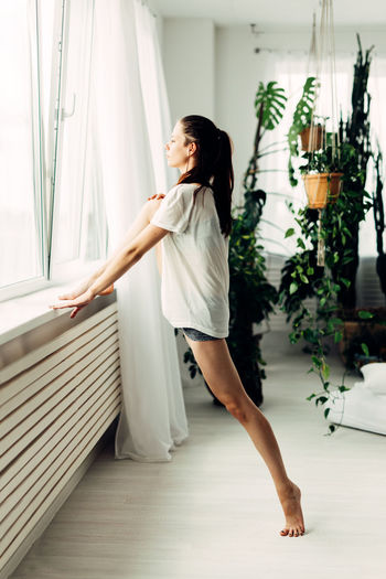 Full Length Side View Of Young Woman Stretching Legs By Window At Home