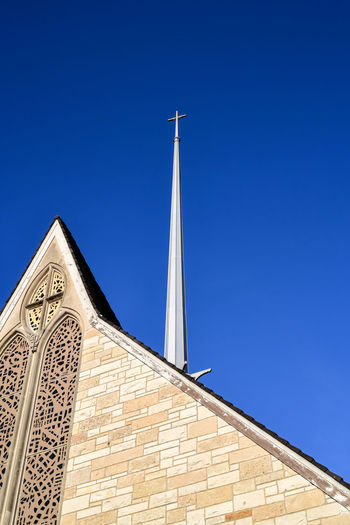 Low angle view of church building against clear blue sky