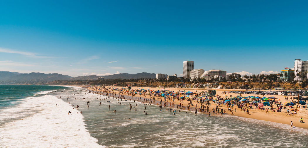 Panoramic view of beach and buildings against blue sky