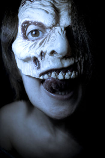 Close-up portrait of shirtless woman wearing spooky mask