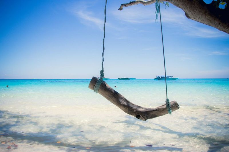 Swing on shore at beach against blue sky
