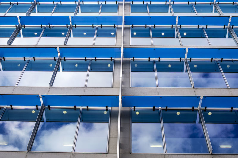 Low angle view of sky reflecting modern glass building