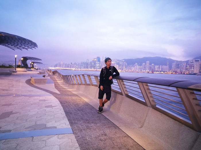 Man on footpath against sky in hong kong city