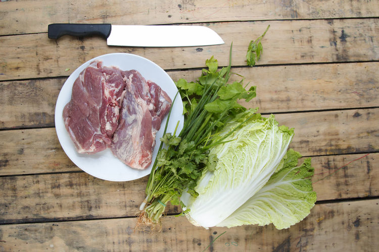 Raw pork and vegetables on wooden table. Chinese Cabbage Chop Cooking Cut Eating Freshness Garlic Pork Raw Red SLICE Background Barbecue Belly Fat Food Fresh Meat Protein Roast Steak Table Vegetables White Wooden
