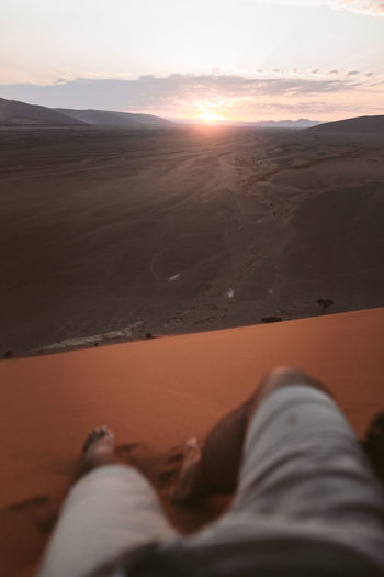 Low section of person relaxing on land against sky during sunset