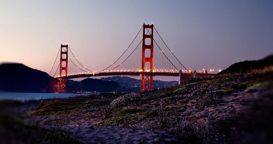 Illuminated golden gate bridge against clear sky