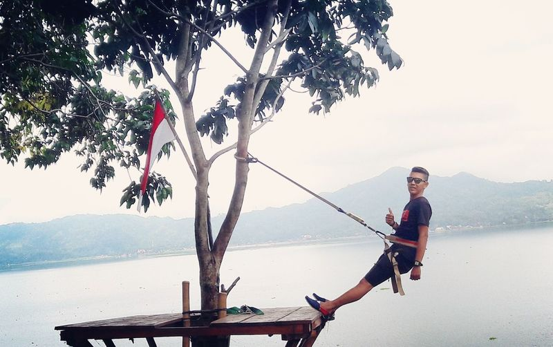 Young man swinging from tree by river against clear sky