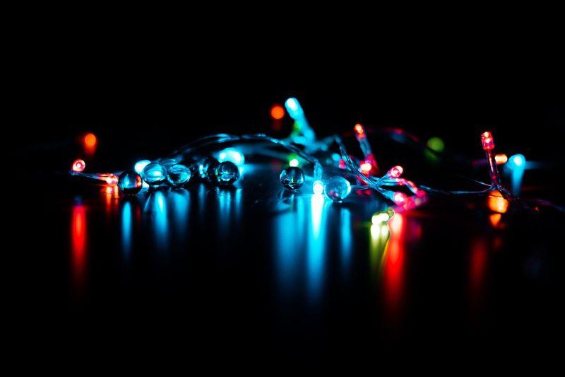Close-up of illuminated lights against black background