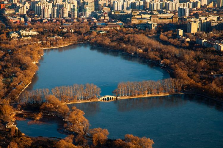 Aerial view of lake in city park during autumn