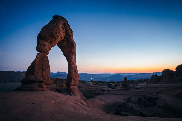 Rock formation on land against sky during sunset