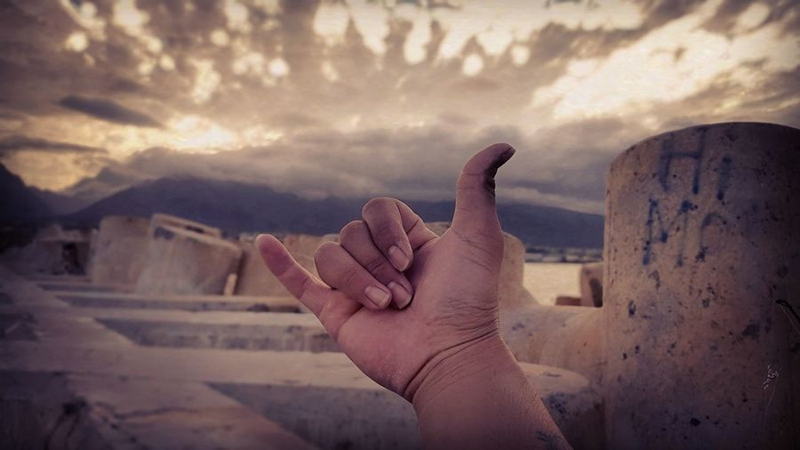 Cropped image of hand showing shaka sign against cloudy sky during sunset
