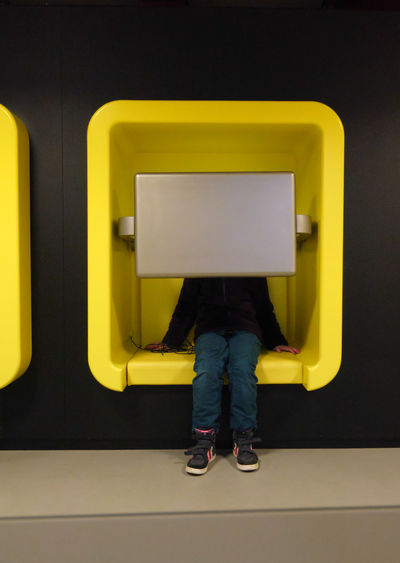 Low section of woman sitting on yellow seat against black background