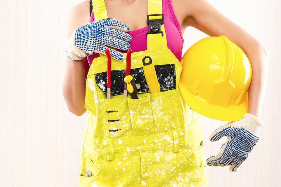 Female construction worker in coverall holding hardhat posing indoors Construction Industry Woman WorkWear Worker Builder Built Structure Caucasian Construction Worker Coverall Employment Female Handywoman Hardhat  Human Job Labor One Person Overall Professional Occupation Protective Workwear Repair Repair Woman Tool Tools