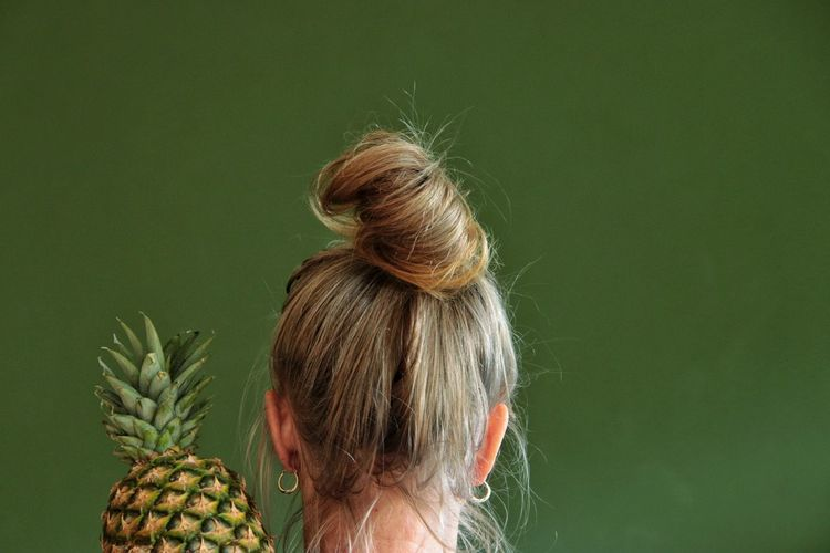 Rear view of woman with pineapple