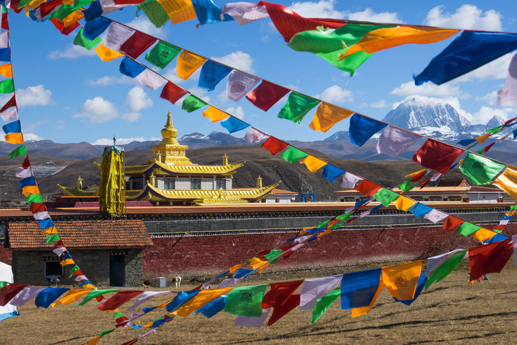 Tagong temple and background Tibetan holy mountain Mt. Yala and Sichuan, China Belief Religion Spirituality Place Of Worship Multi Colored Architecture Flag Built Structure Building Hanging Decoration Building Exterior Sky Cloud - Sky Day No People Outdoors Wind Shrine Tagong China Yala Holy