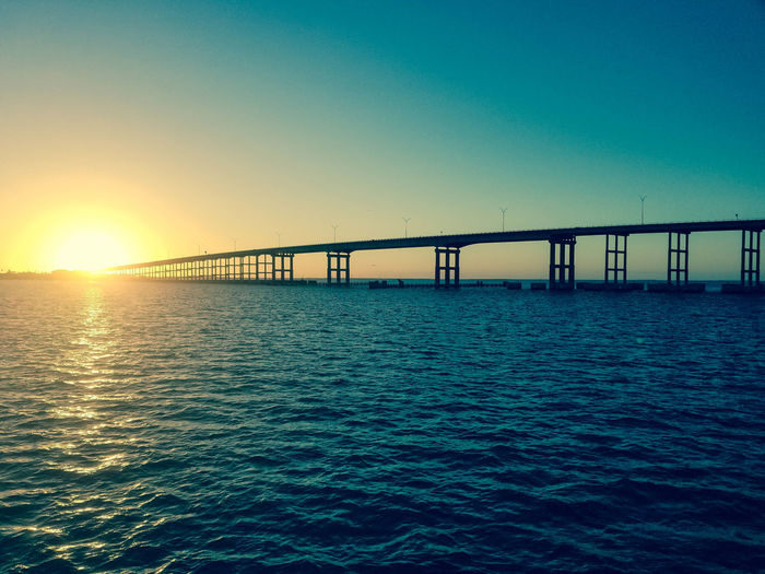 Bridge over sea against clear sky during sunset