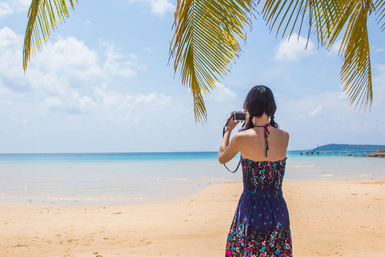 Rear view of young woman photographing beach