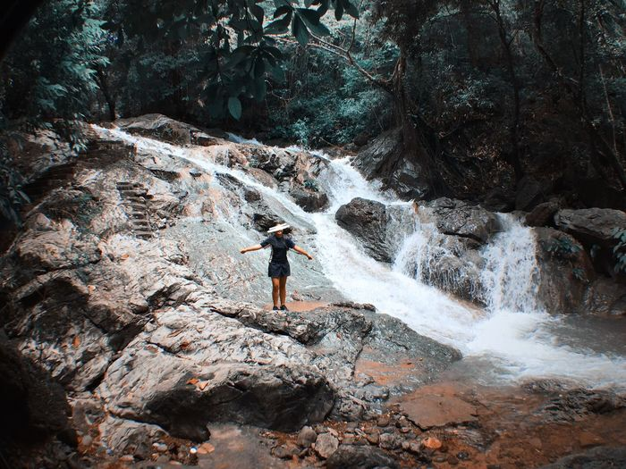 Woman Standing At Waterfall In Forest